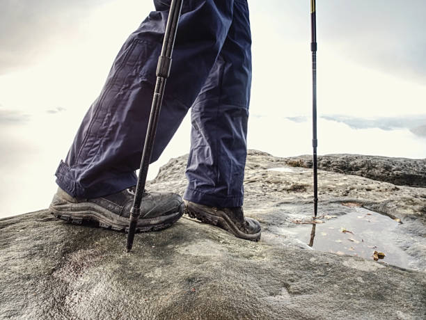 Hiker walks on Trail in warm trousers and waterproof boots stock photo