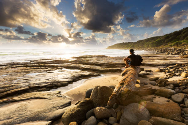 Hiker Watches Explosive Coastal Sunrise stock photo
