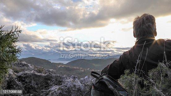 621898406 istock photo Hiker watches the sun rise from mountain ridge 1217058155
