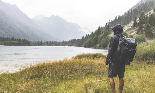 Hiker with a backpack watching the lake sourrounded by mountains stock photo