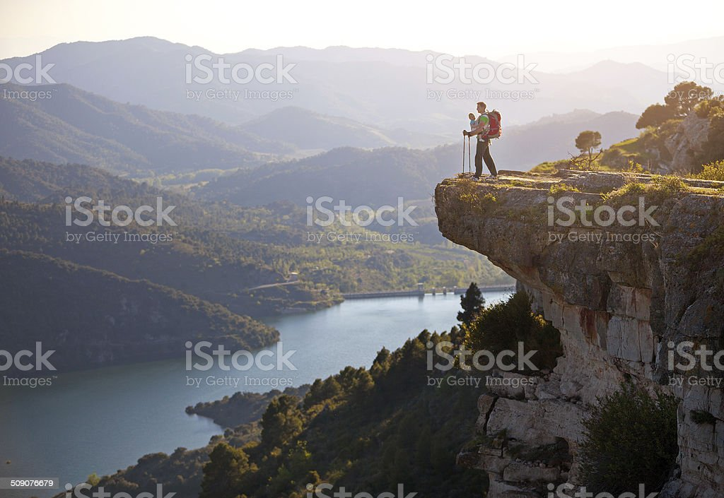 Hiker with baby standing on cliff and enjoying valley view stock photo