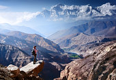 Hiker with Backpack and trekking sticks looks at the beautiful mountain canyon in Upper Mustang. Nepal\nBeautiful inspirational landscape, trekking and activity. Travel sport lifestyle concept