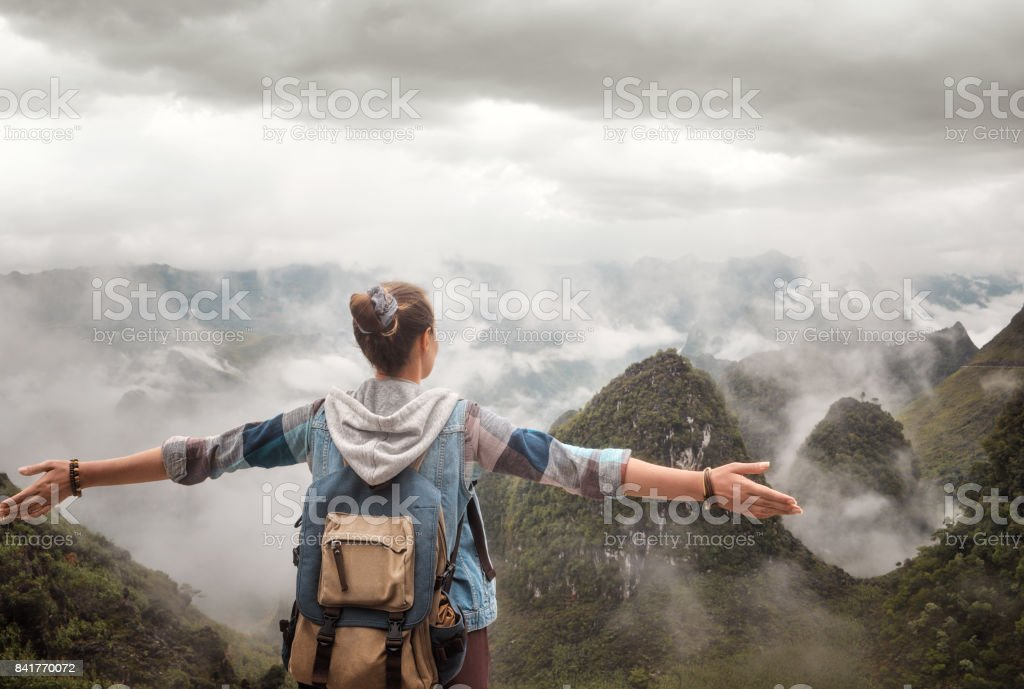 Hiker with backpack in mountains enjoying on view of foggy mountains. stock photo