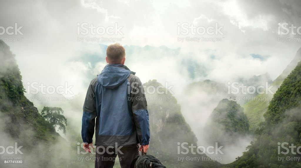 Hiker with backpack in mountains enjoying on view of foggy mountains in North Vietnam. stock photo