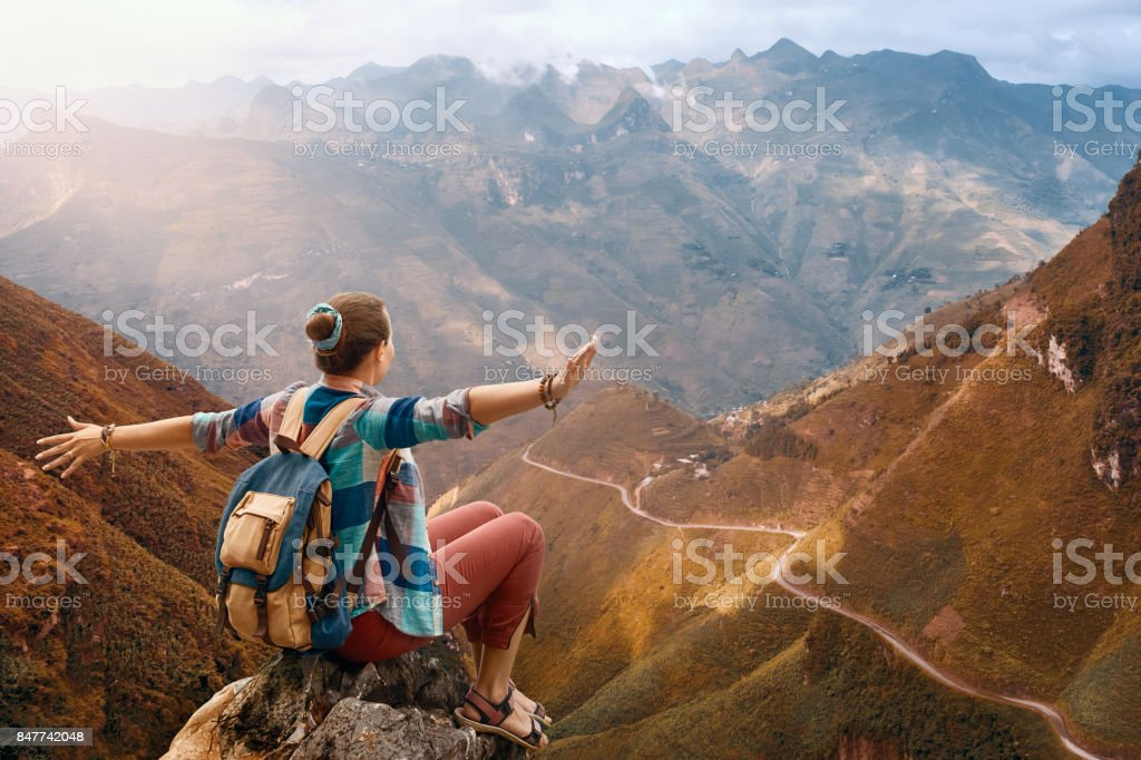 Hiker with backpack in mountains enjoying view at mountains. stock photo