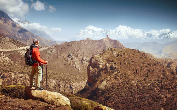 Hiker with backpack looks at the beautiful mountains in Upper Mustang. stock photo