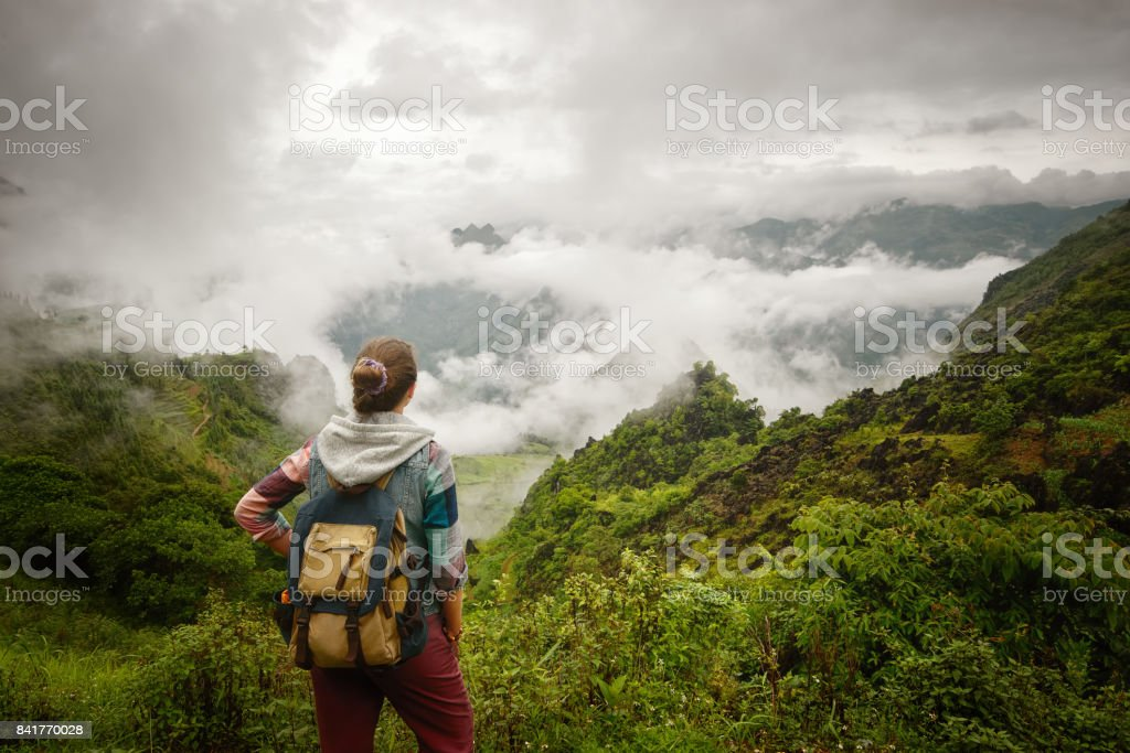 Hiker with backpack relaxing and enjoying on view of foggy mountains. stock photo
