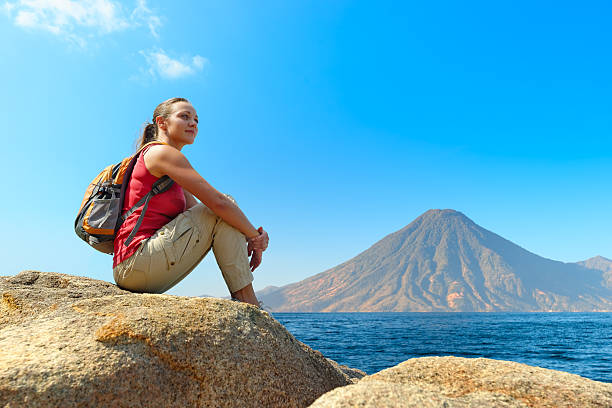 Hiker with backpack relaxing on a rock stock photo