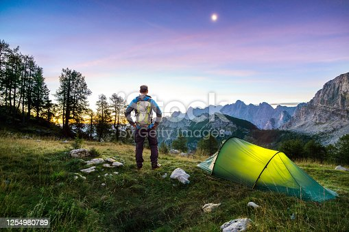 Illuminated camping tent at night and Man with Backpack and hiking equipment. High altitude alpine landscape. Shining Moon in dark blue sky with purple clouds. Julian Alps, Slemenova, Triglav National Park, Slovenia.