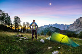 istock Hiker with Backpack standing on Mountain and Tent glowing under a moon night sky at sunset or sunrise twilight hour. Alps, Sleme, Triglav National Park, Slovenia. 1254980789