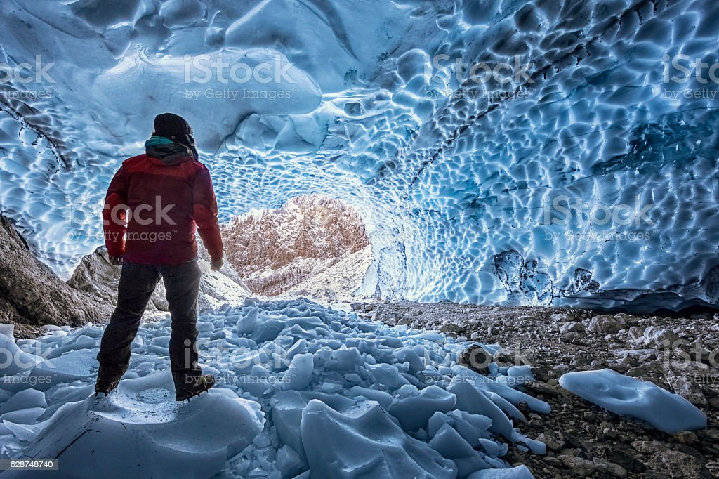 Hiker with crampon looking out of  ice cave - Berchtesgaden stock photo