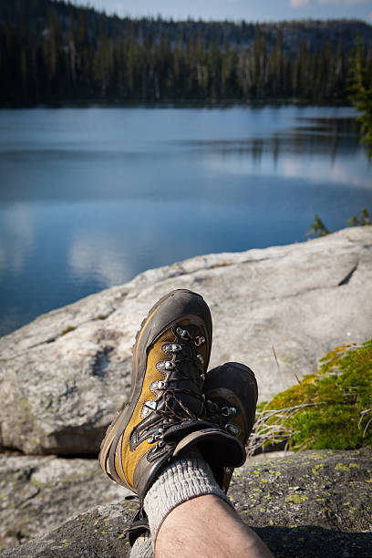 Hiker with his feet up enjoying the view of lake stock photo