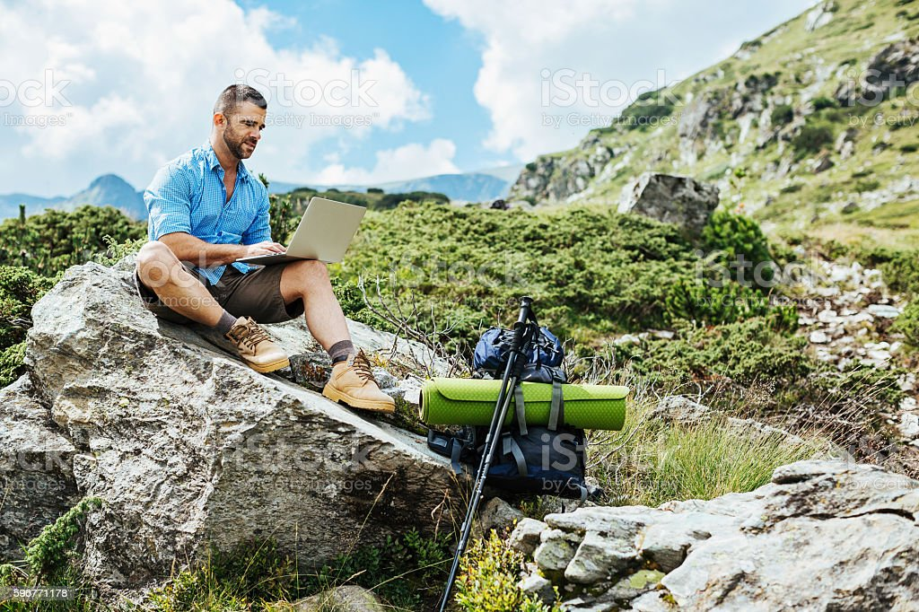 Hiker with laptop sitting on a rock stock photo