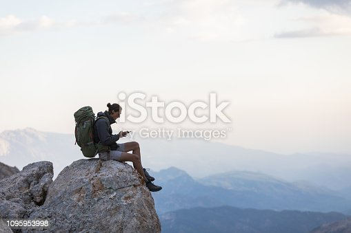 Man sitting at the edge of a cliff using phone.