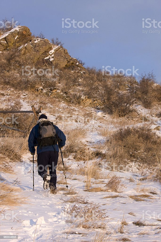 hiker with trekking poles on a snowy mountain trail royalty-free stock photo