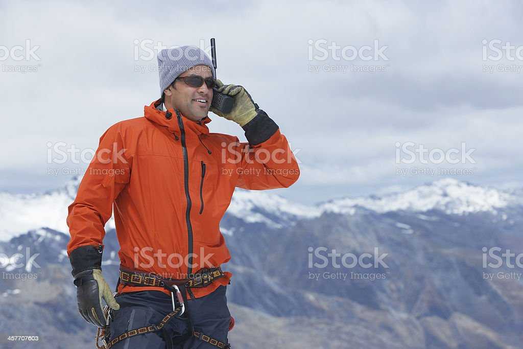 Hiker With Walkie Talkie Against Mountain Peak stock photo
