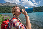 Hiker woman drinking on mountain lake trail from water bottle