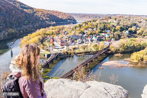Hiker woman girl looking at cityscape overlook, colorful orange yellow foliage fall autumn forest with small village town by river in Harpers Ferry, West Virginia, WV