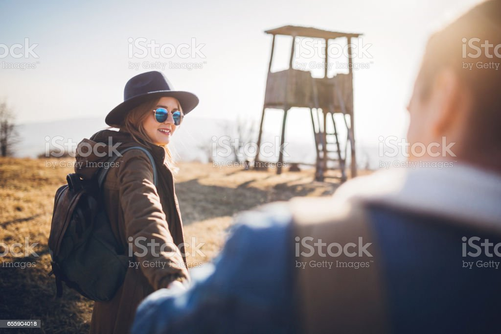 Hiker woman holding her man's hand stock photo