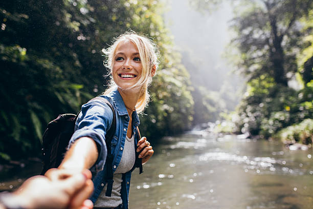 Hiker woman holding man's hand on a nature hike - foto de acervo