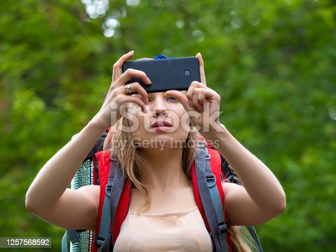 Hiker woman in the forest makes a photo with her phone. Ecotourism concept.