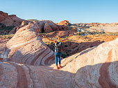 Sporty young woman contemplating wave red sandstone in Valley of fire state park in Las Vegas in Nevada, USA. Girl hiking in nature in the morning