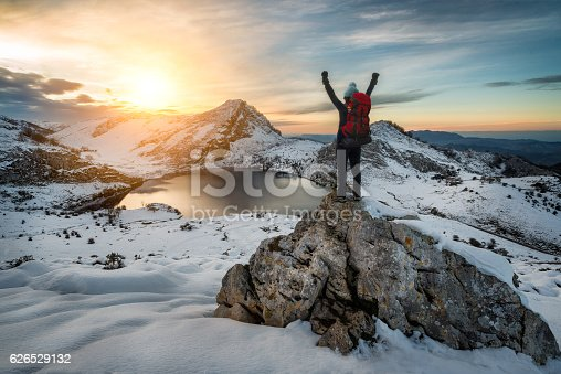 istock Hiker woman rising arms in victory sign on snowy mountain 626529132