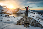 Hiker woman with backpack and hat rising arms in victory sign on snowy mountain peak at Covadonga lake, beautiful snow winter landscape sunset scene on a touristic location of Asturias, Spain, Europe.