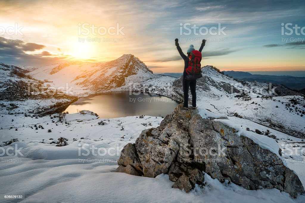 Hiker woman rising arms in victory sign on snowy mountain stock photo