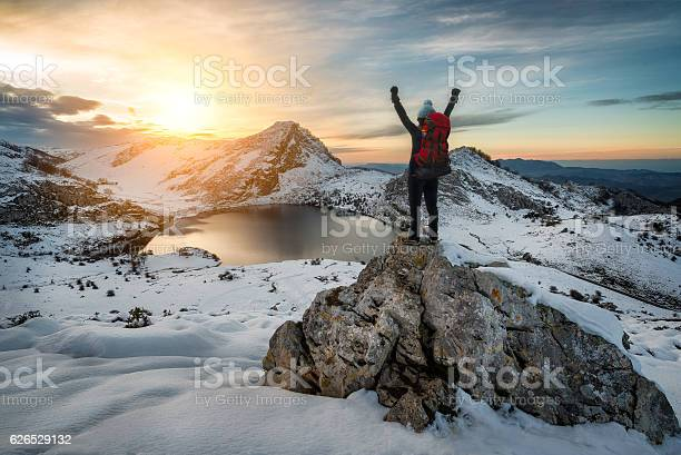 Photo of Hiker woman rising arms in victory sign on snowy mountain
