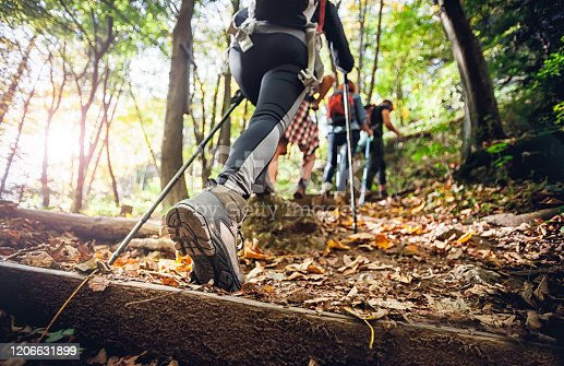 Hiker woman with trekking sticks climbs steep on mountain trail, focus on boot