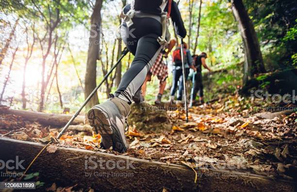 Photo of Hiker woman with trekking sticks climbs steep on mountain trail, focus on boot