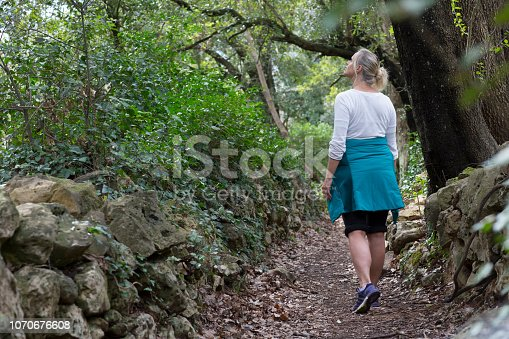She looks up to forest canopy