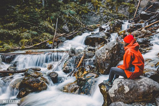 istock Hiker young girl is sitting on a rock near a mountain river. Beautiful nature in the mountains. 861177782