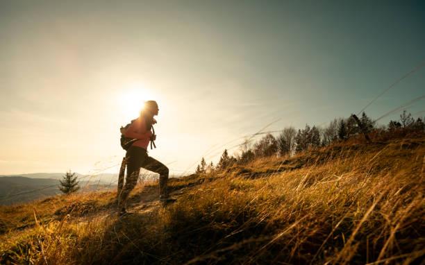 wanderer junge frau mit rucksack steigt auf den berggipfel auf berglandschaft hintergrund - aktiver lebensstil stock-fotos und bilder