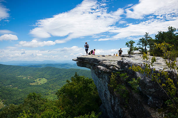 Hikers at McAfee Knob on Appalachian Trail in Virginia Catawba, Virginia, USA - September 1, 2014: Hikers enjoy the view of the Appalachian Mountains from McAfee Knob on Catawba Mountain, near Roanoke, Virginia. It is one of the most popular overlooks on the Appalachian Trail and is situated at an elevation is 3,171 feet. appalachian trail stock pictures, royalty-free photos & images