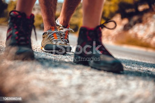 istock Hikers boots on a mountain road 1063696346
