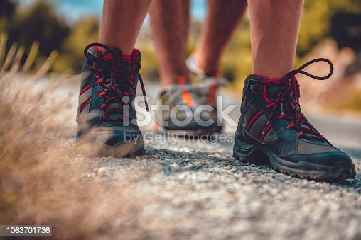 istock Hikers boots on a mountain road 1063701736