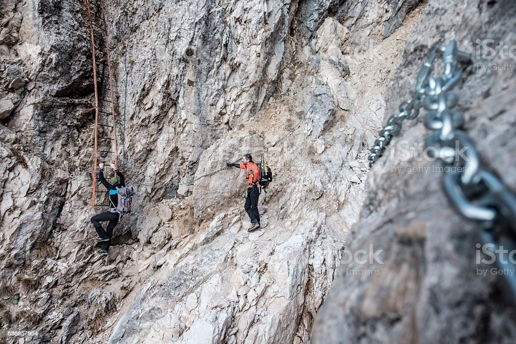 Hikers climb mountain on equipped trail stock photo