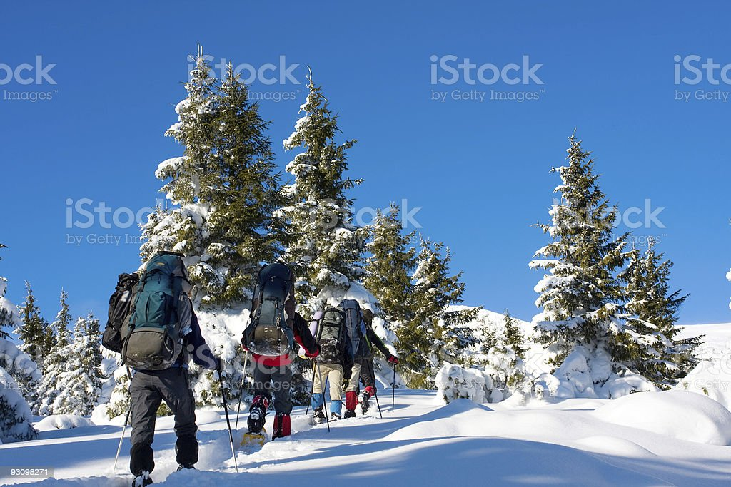 Hikers climbing a snowy mountain on a sunny day stock photo