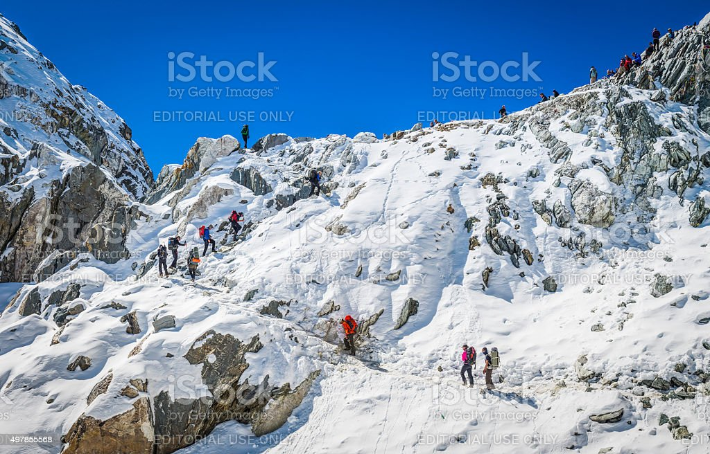 Hikers climbing pass high in snowy mountains Khumbu Himalaya Nepal stock photo