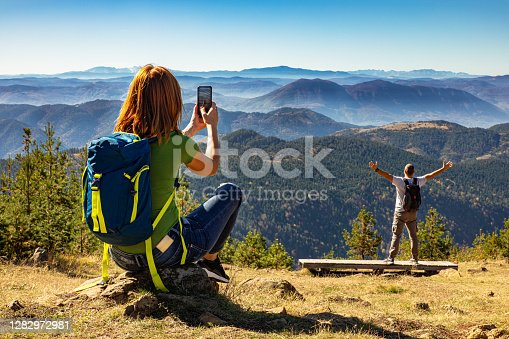 Hikers couple with backpack on top of the mountain, woman photographing her husband with phone.