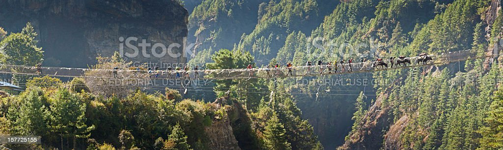 Hikers crossing canyon rope bridge Himalayas Nepal stock photo