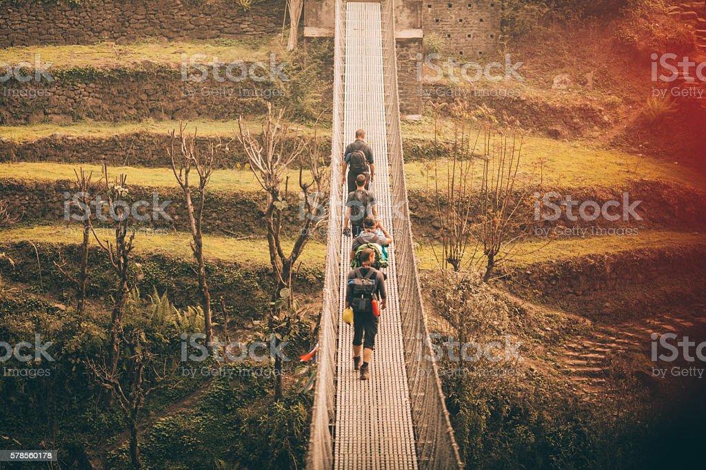 Hikers crossing the footbridge stock photo
