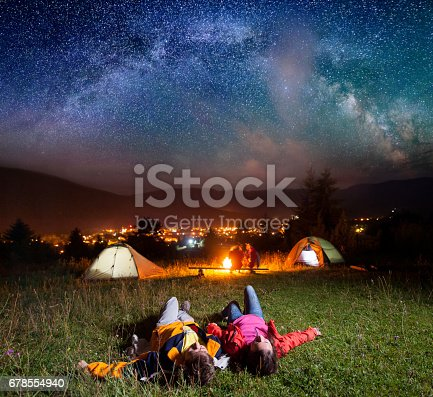 678554980 istock photo Hikers enjoying the bright stars and lying on the grass 678554940