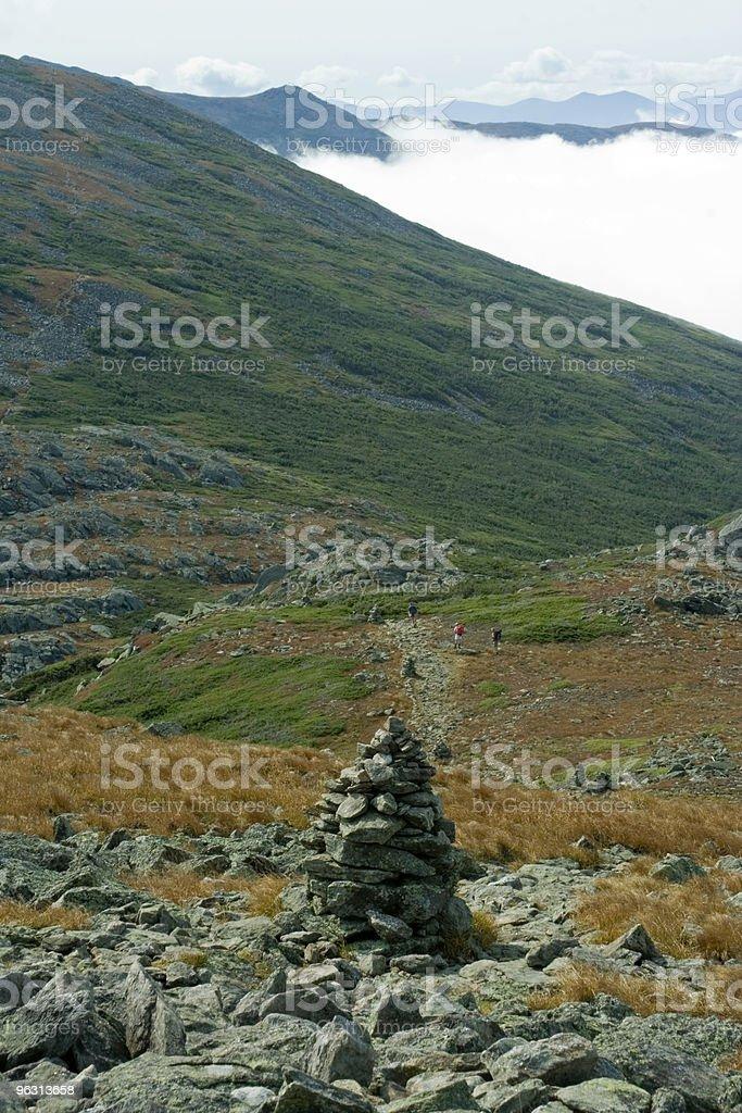 Hikers follow cairns - Royaltyfri Avskildhet Bildbanksbilder