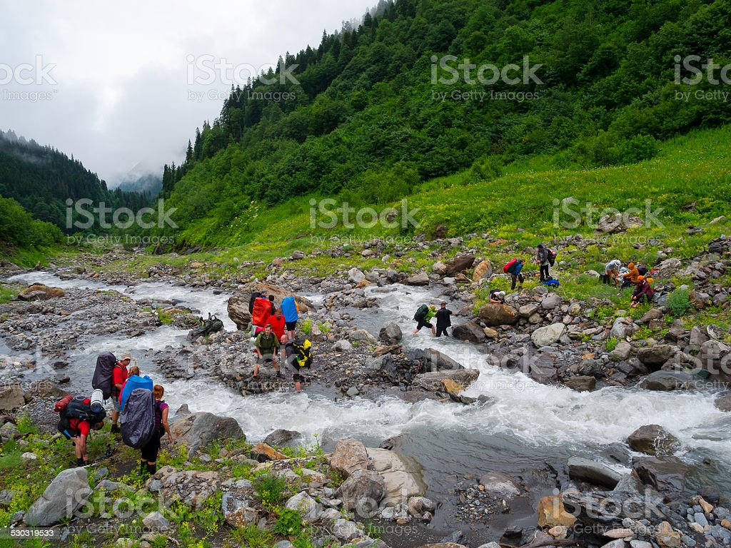 Hikers group cross the mountain river stock photo