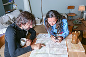 couple of hikers planning the route sitting around a table pointing the route in a map in a welcoming shelter - focus on the young woman