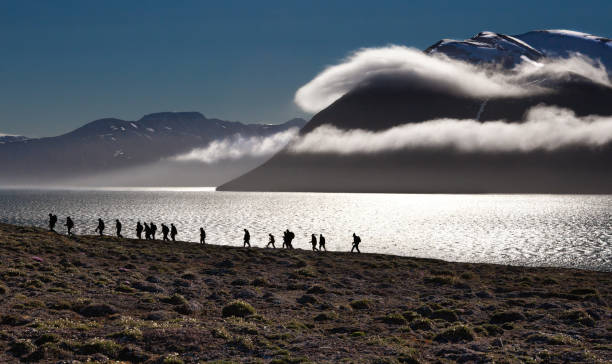 Hikers in Svalbard, Norway, with Dramatic Clouds stock photo