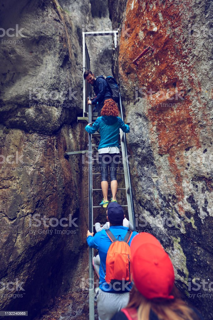 rear view of friends in the mountain moving up on stairs and enjoying...